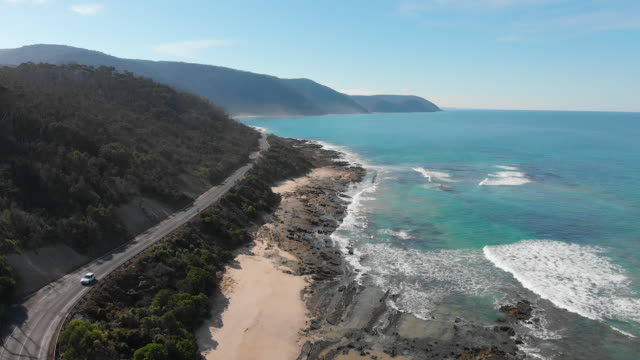 4k aerial of a car driving along the great ocean road, victoria - exploration stock videos & royalty-free footage