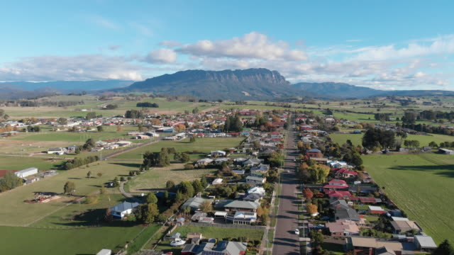 4k aerial of a car driving the main street of a country town in the foothills beneath an impressive mountain range - town stock videos & royalty-free footage