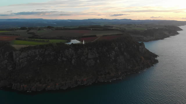 4k aerial of a lighthouse perched high on a cliff overlooking the ocean at dusk - lighthouse stock videos & royalty-free footage