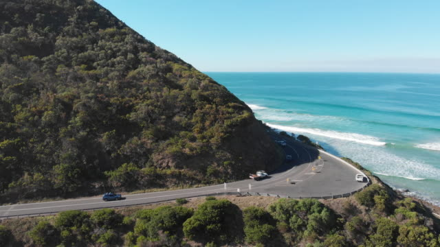4k aerial of a line of cars travelling along the great ocean road, victoria - exploration stock videos & royalty-free footage