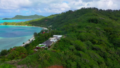 aerial of a luxurious house on a beautiful tropical island, done flying forward then tilting down over the house - bora bora, french polynesia - coastal feature stock videos & royalty-free footage
