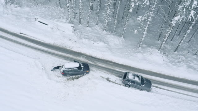 aerial of a man successfully pushing the car out of snow - 押す点の映像素材/bロール