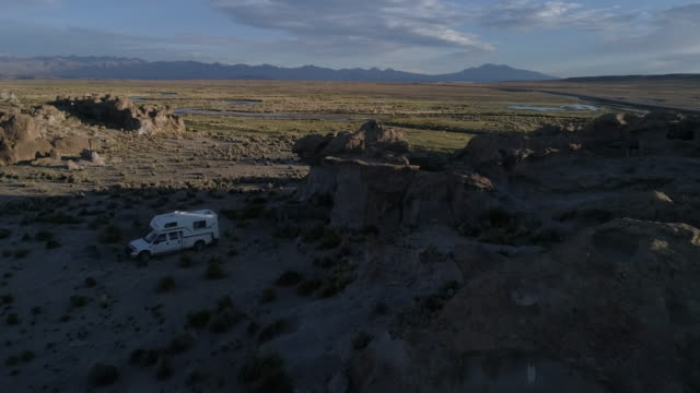 aerial of a pick up camper standing in a river and rocky landscape in the andean mountains - canyon stock videos & royalty-free footage