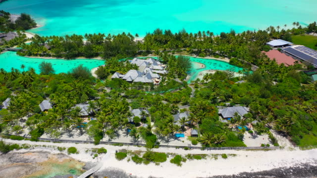 vidéos et rushes de aerial of a resort on a beautiful tropical island with helicopter landing pad in a bright blue lagoon, drone flying forward while slowly descending - bora bora, french polynesia - bora bora