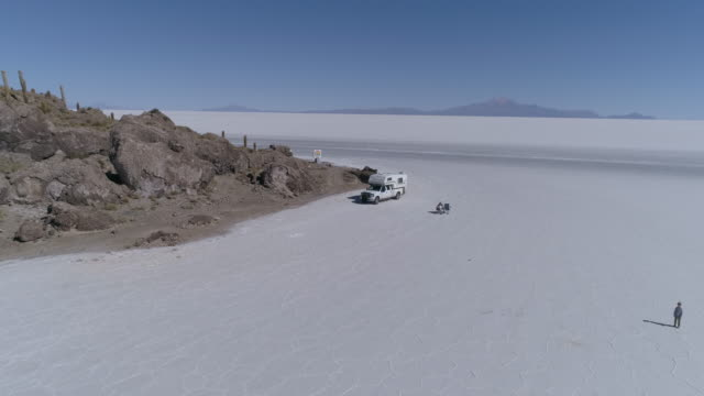 aerial of a salt lake with mountains, people and  a pickup camper - kaktus stock-videos und b-roll-filmmaterial
