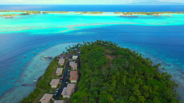 vidéos et rushes de aerial of a scenic ruin wall on a beautiful tropical island, drone flying backwards passing over the wall - bora bora, french polynesia - bora bora