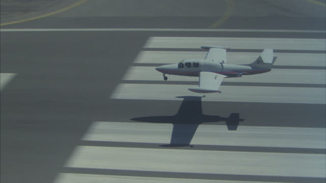 Aerial of a small private jet flying over fields, touching down on an airport runway, then taking off again.