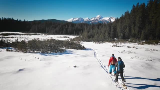 Aerial of a snow path and mountaineers walking on it