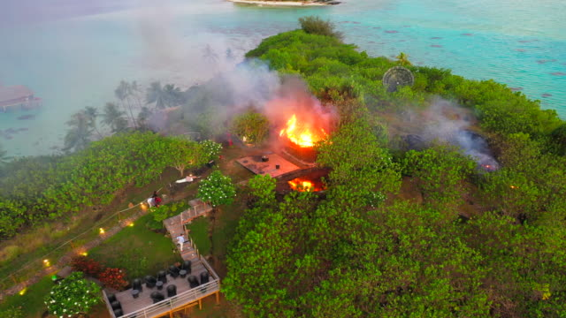 aerial of a straw hut burning on a beautiful tropical island, drone flying from right to left then backwards then turning from right to left away from the fire - bora bora, french polynesia - フランス領ポリネシア点の映像素材/bロール
