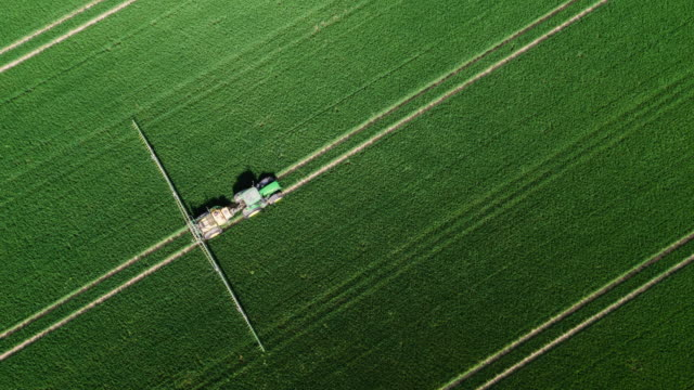 aerial of a tractor spraying pesticides - tractor stock videos & royalty-free footage