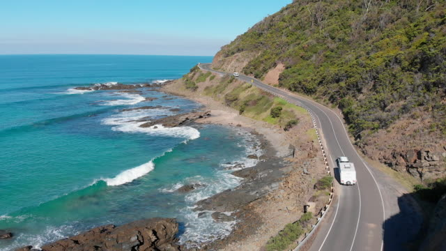 4k aerial of a van followed by a car towing a caravan travelling along the great ocean road, victoria - coastal road stock videos & royalty-free footage