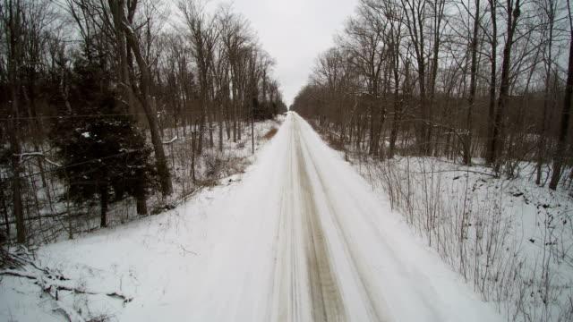 Luchtfoto van een witte bestelwagen op een landweg in de Winter