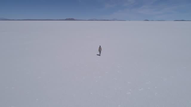 aerial of a woman walking on the salt lake salar de uyuni - loneliness stock videos & royalty-free footage