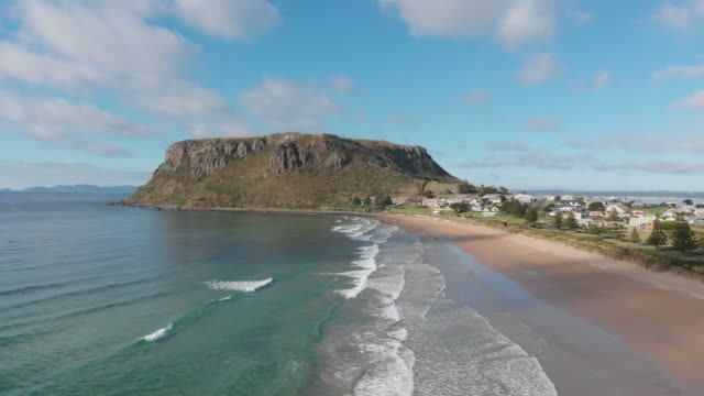 4K aerial of a woman walking the beach beneath 'The Nut' towering over the picturesque town of Stanly on the far north western coast of Tasmania