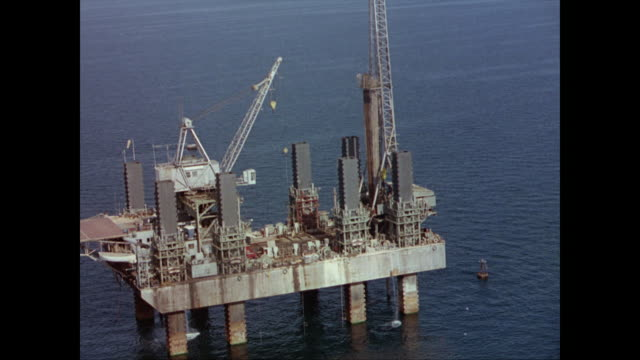 aerial of abandoned wrecked offshore drilling platform / helicopter lands on offshore oil platform men working on the platform drilling for oil - 1965 stock videos & royalty-free footage