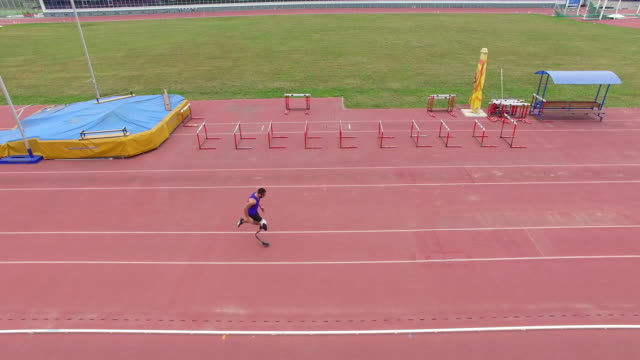 aerial of adaptive athlete practicing long jump at stadium - artificial limb stock videos & royalty-free footage