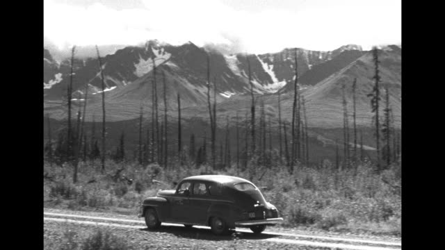 aerial of alaska highway cut out among forested landscape / pan over mountain range w tiny car driving on hwy in fg / chevy coupe driving away from... - whitehorse stock videos and b-roll footage