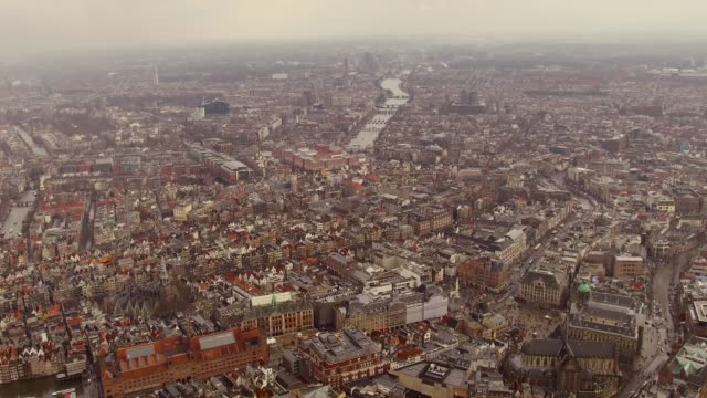 aerial of amsterdam center over looking tops of houses and buildings, canals - opernhaus stock-videos und b-roll-filmmaterial