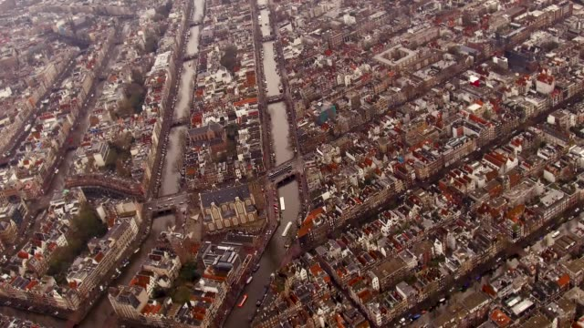 aerial of amsterdam center over looking tops of houses and buildings, canals - veduta dall'alto video stock e b–roll