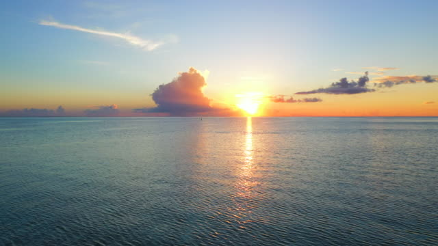 vídeos de stock, filmes e b-roll de aerial of an amazing sunset over the ocean, drone flying forward towards the horizon - bora bora, french polynesia - boa postura