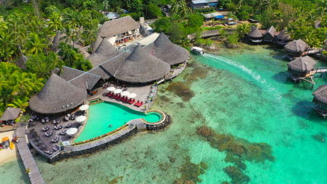 vidéos et rushes de aerial of an amazing tropical area, drone flying forward then turning from left to right, showing overwater bungalows under construction - bora bora, french polynesia - bora bora