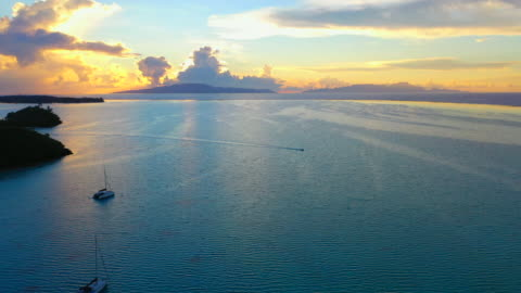 aerial of an awesome sunset over the ocean, drone flying forward then turning from left to right and tilting down while descending to follow a boat - bora bora, french polynesia - kameralutning bildbanksvideor och videomaterial från bakom kulisserna