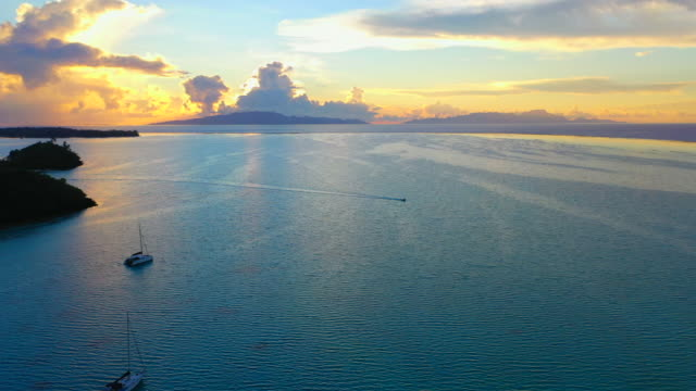 aerial of an awesome sunset over the ocean, drone flying forward then turning from left to right and tilting down while descending to follow a boat - bora bora, french polynesia - schrägansicht stock-videos und b-roll-filmmaterial