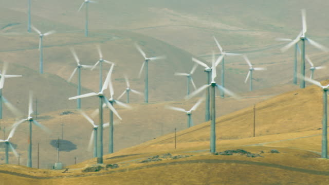 aerial of array of wind turbines - energia rinnovabile video stock e b–roll