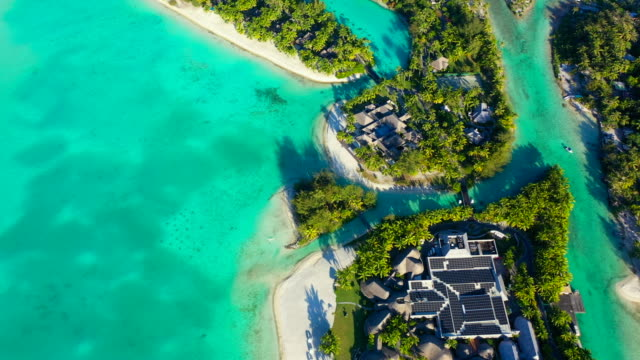 vidéos et rushes de aerial of beautiful tropical islands with helicopter landing pad in a bright blue lagoon, drone tilting down then flying forward - bora bora, french polynesia - bora bora