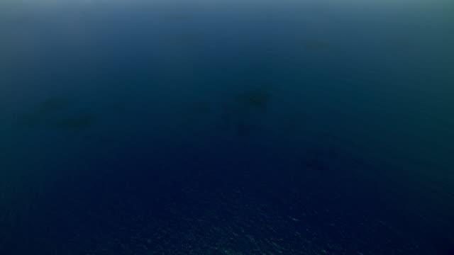 Aerial of blue Caribbean ocean with Montserrat Island in far distance.