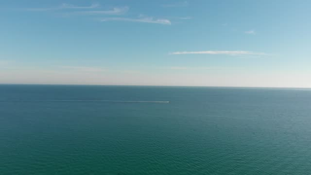 4k aerial of blue sea and a jet ski zooming in the distance - sense stock-videos und b-roll-filmmaterial