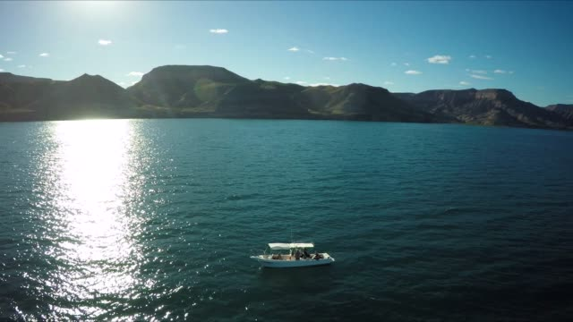 aerial of boat at sea, coast in background - bay of water stock videos & royalty-free footage