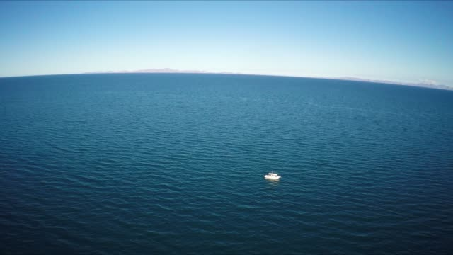 aerial of boat at sea, extreme wide shot - orizzonte sull'acqua video stock e b–roll