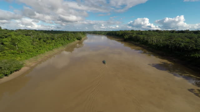 Aerial of boat moving along Amazon River