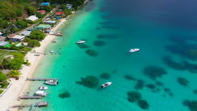 vídeos de stock e filmes b-roll de aerial of boats floating on bright blue water by beautiful topical beach, drone flying forward along the beach - bora bora, french polynesia - ilhas do pacífico