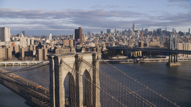 aerial of brooklyn bridge. east river. new york city skyline with skyscrapers and high rise office or apartment buildings. american flag. manhattan bridge in bg.
