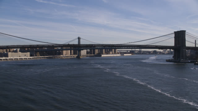 aerial of brooklyn bridge over east river. manhatan bridge and midtown manhattan new york city skyline in bg. american flag.