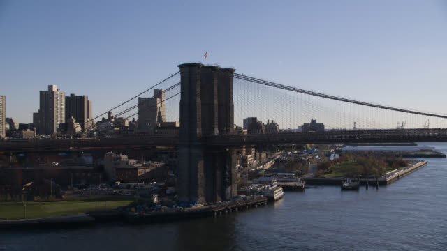 aerial of brooklyn bridge with american flag, over east river. broklyn and downtown manhattan new york city skyline in bg. skyscrapers and high rise office or apartment buildings.