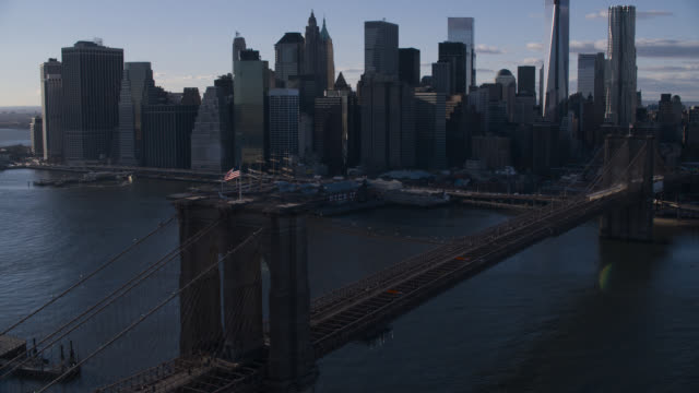 aerial of brooklyn bridge with american flag, over east river. downtown manhattan new york city skyline in bg. skyscrapers and high rise office or apartment buildings.