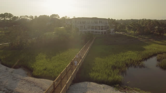 aerial of camera flying over dock by a luxury home with a group of people walking - reed grass family stock videos & royalty-free footage
