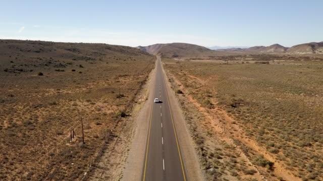 biltrafikanten ner för en lång grusväg i öppet landskap - karoo bildbanksvideor och videomaterial från bakom kulisserna