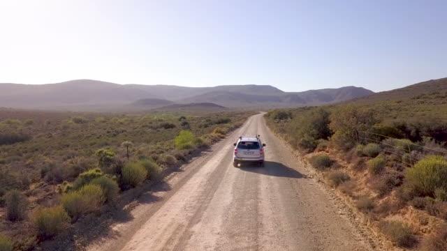 antenne des wagens auf einem langen schotterstraße - republik südafrika stock-videos und b-roll-filmmaterial