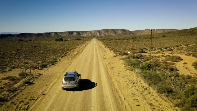 aerial of car travelling down lonely road in the landscape
