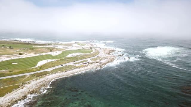 Antenne des Autos fahren entlang Ozean Küste neben Golfplatz