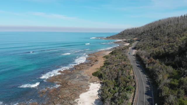 4k aerial of cars travelling along the great ocean road, victoria - coastal road stock videos & royalty-free footage