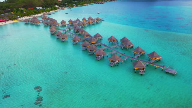 vidéos et rushes de aerial of charming overwater bungalows in a beautiful blue lagoon, drone flying forward then tilting down showing top view of the bungalows - bora bora, french polynesia - bora bora