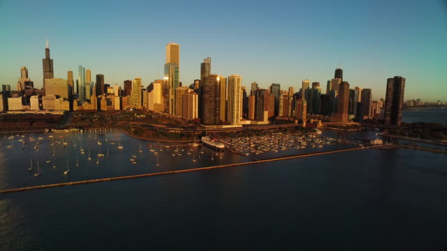 Aerial of Chicago skyline at sunrise facing northwest pulling back over harbor