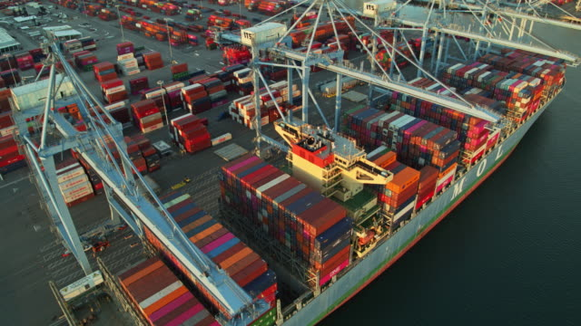 aerial of cranes and ships moored around container terminal - port of los angeles stock videos & royalty-free footage