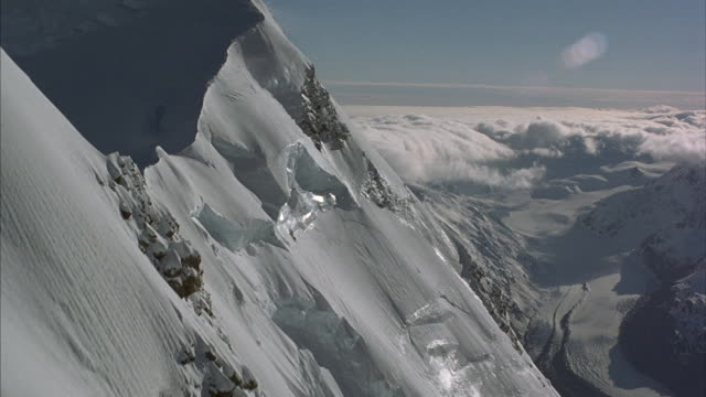 aerial of deep snow covering steep mountain sides. - high up stock videos & royalty-free footage