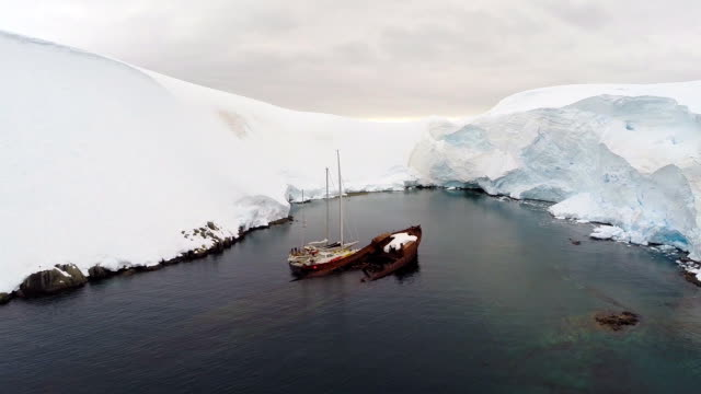 aerial of derelict sunker ship in a bay among scenery of antarctica - landscape scenery点の映像素材/bロール